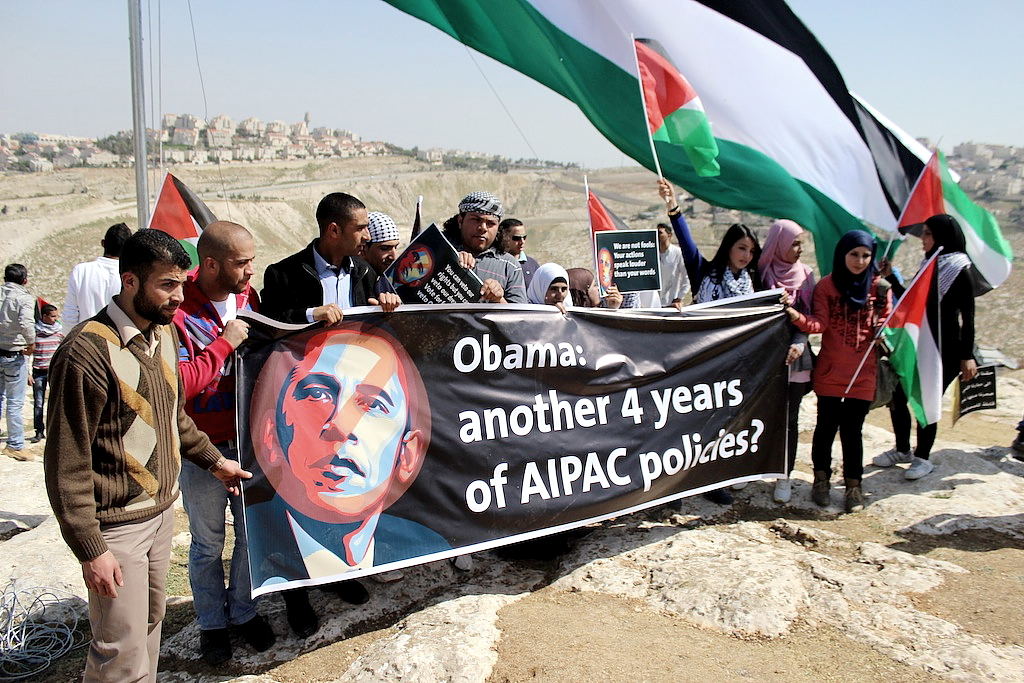 Photo by Andrew Beale—Demonstrators in Ahfad Younis stand in front of a large Palestinian flag holding a sign referring to Obama's support for policies advocated by  a pro-Israel lobbying group. In the upper left, the Israeli settlement Ma'ale Adumim can be seen on the hilltop.