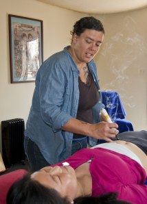 Perez administers moxibustion therapy—a traditional Chinese method promoting circulation and relaxation—to Rachel Cheng. — Photo by Margaret Wright