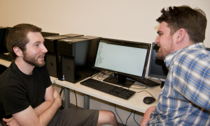 Jeffrey Knockel (left) and his advisor, Assistant Professor Jed Crandall (right) chat in one of UNM's computer engineering labs. The two devised a method to weed out words that can trigger online censorship in China. Photo by Margaret Wright