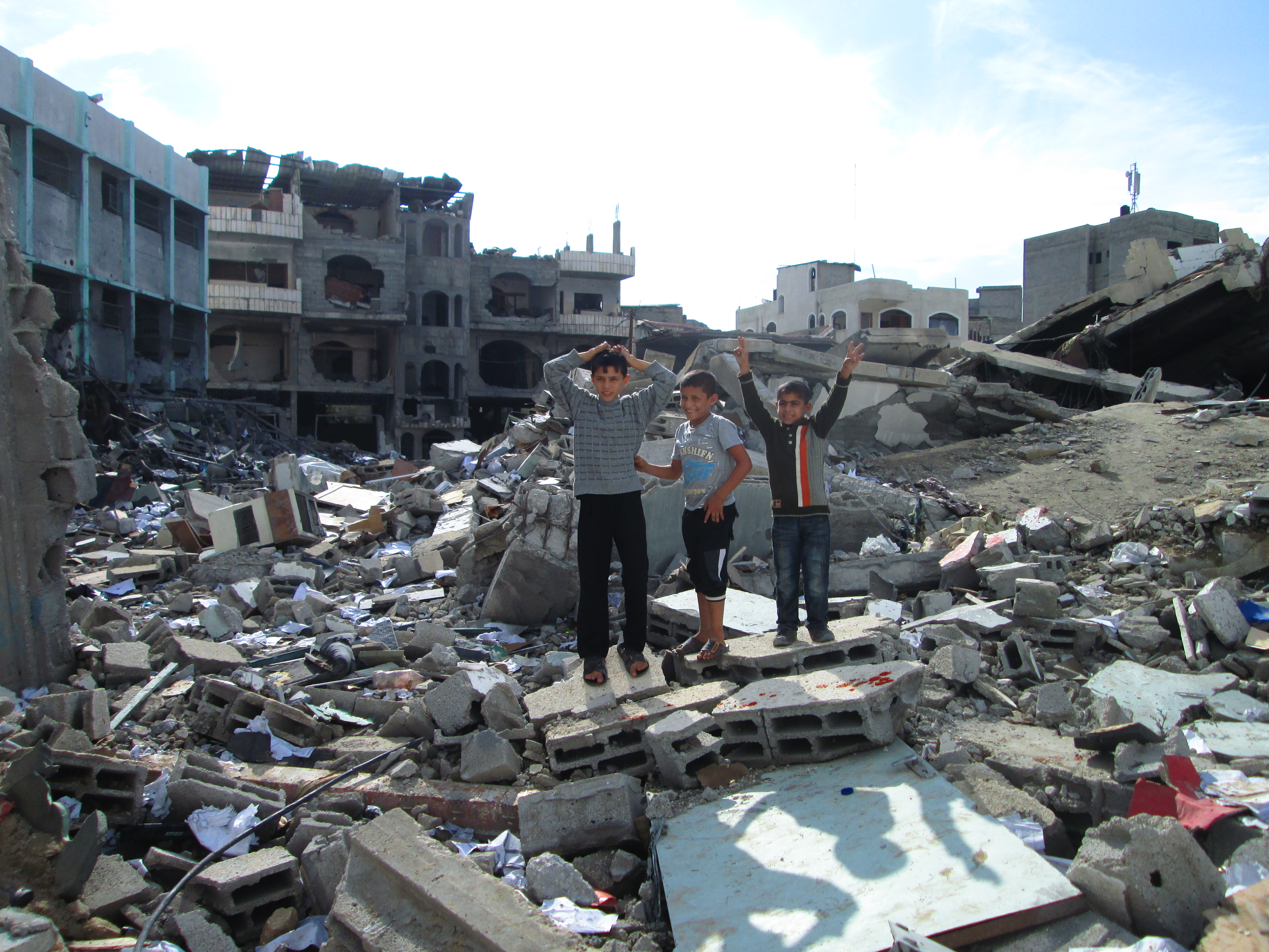 Gazan children pose on the ruins of the bombed Ministry of the Interior office (an entirely civilian building) in Gaza city three days after the end of Israel's bombing campaign. —Photo by Andy Beale